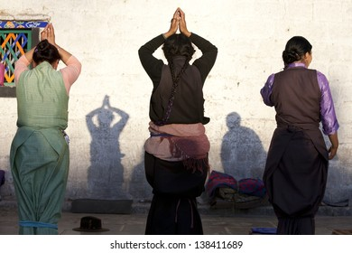 LHASA, TIBET-OCTOBER 08: Female Tibetan buddhist pilgrims are praying in front of Jokhang Temple on October 08, 2012 in Lhasa, Tibet.