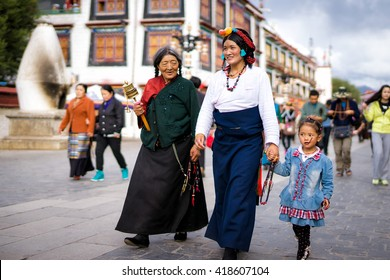 LHASA/CHINA - SEPTEMBER 5, 2014: Three generations of tibetan woman walk at the Barkhor street in Lhasa, Tibet, China
