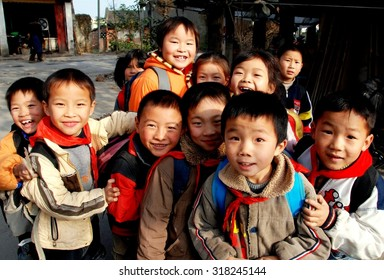 Li'an Village, China - November 26, 2007:  A group of smiling Chinese children wearing their regulation red scarves gather outside their school