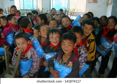 LIANGSHAN, CHINA - MAY 29: Unidentified children smile and laugh when they get their presents of Childrens Day, which donated by welfare organization on May 29, 2013, Liangshan, Sichuan, China