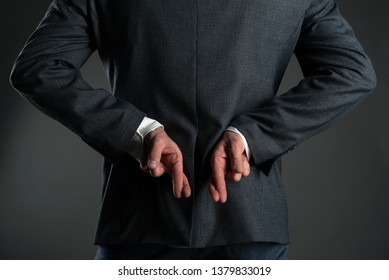 The liar business man. A man with crossed finger behind his back is giving a false promises concept. Deceitful person.