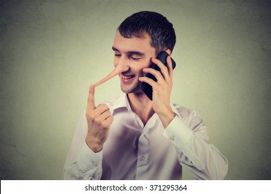 Liar customer service representative. Happy young man with long nose talking on mobile phone isolated on gray wall background. Liar concept. Human face expressions emotion feelings, character traits