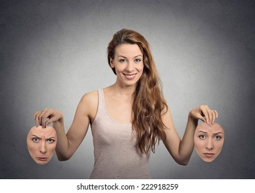 Liar. Portrait beautiful happy girl holds two masks isolated grey wall background. Human face expressions, emotions, feelings, bipolar state of mind concept
