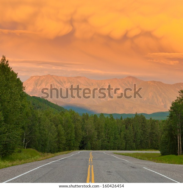 Liard River valley Alaska Highway  British Columbia  Canada  sunset light on approaching summer thunderstorm clouds