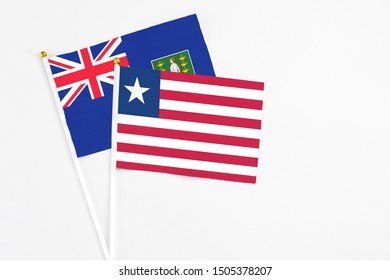 Liberia and British Virgin Islands stick flags on white background. High quality fabric, miniature national flag. Peaceful global concept.White floor for copy space.