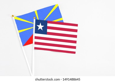 Liberia and Reunion stick flags on white background. High quality fabric, miniature national flag. Peaceful global concept.White floor for copy space.