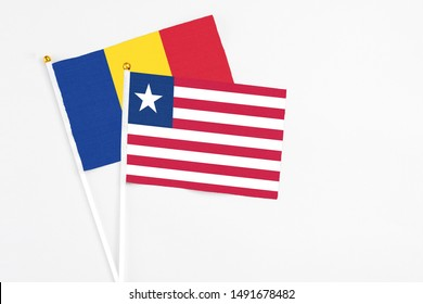 Liberia and Romania stick flags on white background. High quality fabric, miniature national flag. Peaceful global concept.White floor for copy space.