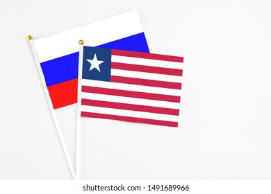 Liberia and Russia stick flags on white background. High quality fabric, miniature national flag. Peaceful global concept.White floor for copy space.