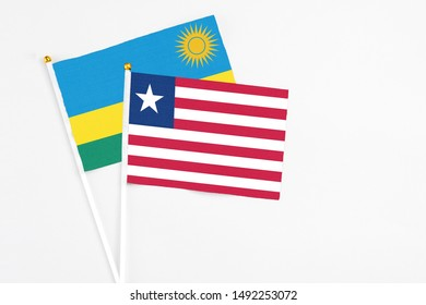 Liberia and Rwanda stick flags on white background. High quality fabric, miniature national flag. Peaceful global concept.White floor for copy space.