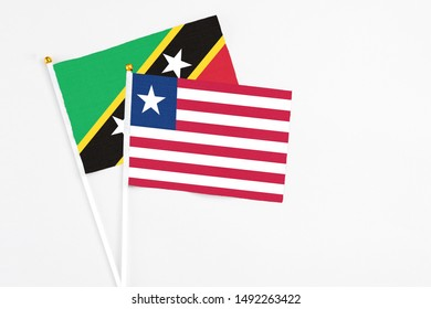 Liberia and Saint Kitts And Nevis stick flags on white background. High quality fabric, miniature national flag. Peaceful global concept.White floor for copy space.