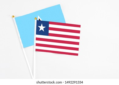 Liberia and Saint Lucia stick flags on white background. High quality fabric, miniature national flag. Peaceful global concept.White floor for copy space.