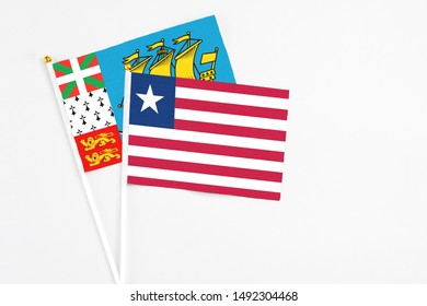 Liberia and Saint Pierre And Miquelon stick flags on white background. High quality fabric, miniature national flag. Peaceful global concept.White floor for copy space.