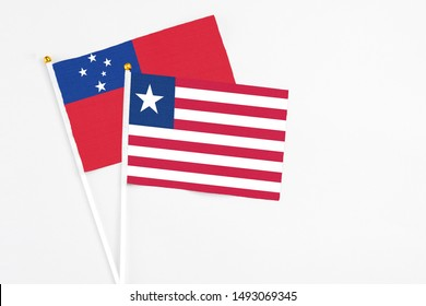 Liberia and Samoa stick flags on white background. High quality fabric, miniature national flag. Peaceful global concept.White floor for copy space.