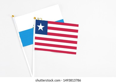 Liberia and San Marino stick flags on white background. High quality fabric, miniature national flag. Peaceful global concept.White floor for copy space.