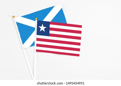 Liberia and Scotland stick flags on white background. High quality fabric, miniature national flag. Peaceful global concept.White floor for copy space.