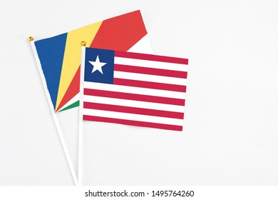 Liberia and Seychelles stick flags on white background. High quality fabric, miniature national flag. Peaceful global concept.White floor for copy space.v