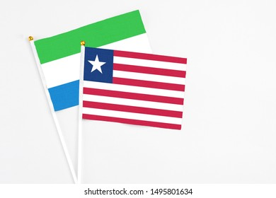 Liberia and Sierra Leone stick flags on white background. High quality fabric, miniature national flag. Peaceful global concept.White floor for copy space.