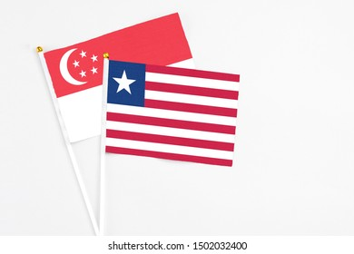 Liberia and Singapore stick flags on white background. High quality fabric, miniature national flag. Peaceful global concept.White floor for copy space.