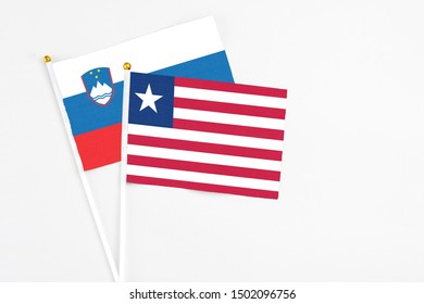 Liberia and Slovenia stick flags on white background. High quality fabric, miniature national flag. Peaceful global concept.White floor for copy space.