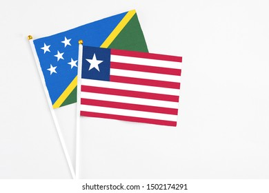 Liberia and Solomon Islands stick flags on white background. High quality fabric, miniature national flag. Peaceful global concept.White floor for copy space.