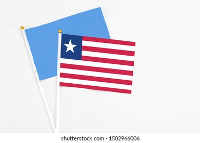 Liberia and Somalia stick flags on white background. High quality fabric, miniature national flag. Peaceful global concept.White floor for copy space.