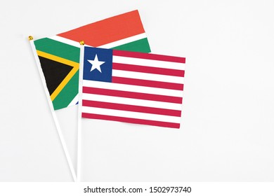Liberia and South Africa stick flags on white background. High quality fabric, miniature national flag. Peaceful global concept.White floor for copy space.