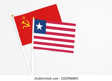 Liberia and Soviet Union stick flags on white background. High quality fabric, miniature national flag. Peaceful global concept.White floor for copy space.