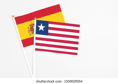 Liberia and Spain stick flags on white background. High quality fabric, miniature national flag. Peaceful global concept.White floor for copy space.