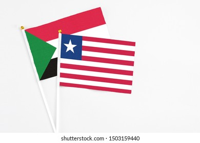 Liberia and Sudan stick flags on white background. High quality fabric, miniature national flag. Peaceful global concept.White floor for copy space.