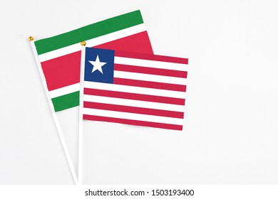 Liberia and Suriname stick flags on white background. High quality fabric, miniature national flag. Peaceful global concept.White floor for copy space.