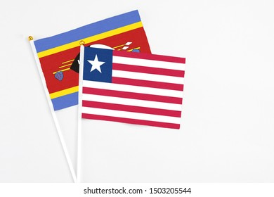 Liberia and Swaziland stick flags on white background. High quality fabric, miniature national flag. Peaceful global concept.White floor for copy space.