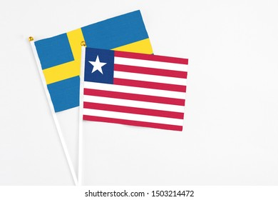 Liberia and Sweden stick flags on white background. High quality fabric, miniature national flag. Peaceful global concept.White floor for copy space.