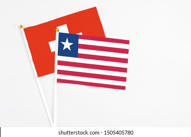Liberia and Switzerland stick flags on white background. High quality fabric, miniature national flag. Peaceful global concept.White floor for copy space.