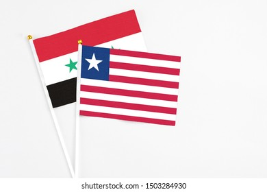 Liberia and Syria stick flags on white background. High quality fabric, miniature national flag. Peaceful global concept.White floor for copy space.