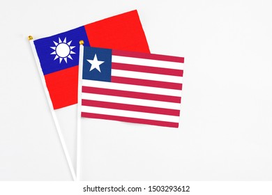 Liberia and Taiwan stick flags on white background. High quality fabric, miniature national flag. Peaceful global concept.White floor for copy space.
