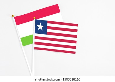 Liberia and Tajikistan stick flags on white background. High quality fabric, miniature national flag. Peaceful global concept.White floor for copy space.