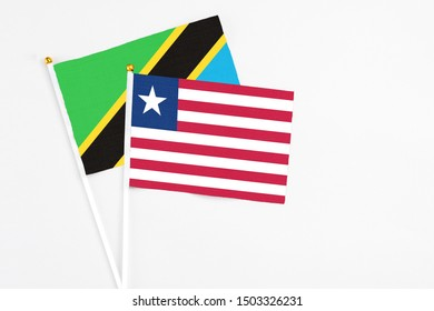 Liberia and Tanzania stick flags on white background. High quality fabric, miniature national flag. Peaceful global concept.White floor for copy space.