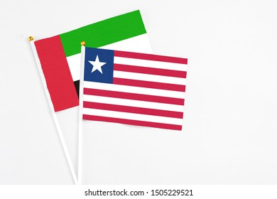 Liberia and United Arab Emirates stick flags on white background. High quality fabric, miniature national flag. Peaceful global concept.White floor for copy space.
