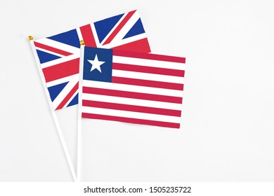 Liberia and United Kingdom stick flags on white background. High quality fabric, miniature national flag. Peaceful global concept.White floor for copy space.