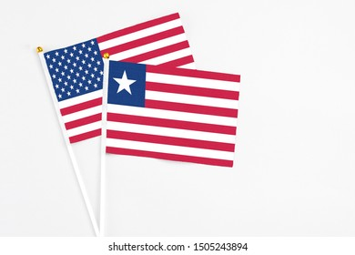 Liberia and United States stick flags on white background. High quality fabric, miniature national flag. Peaceful global concept.White floor for copy space.