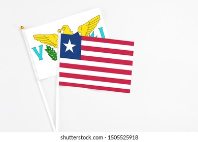 Liberia and United States Virgin Islands stick flags on white background. High quality fabric, miniature national flag. Peaceful global concept.White floor for copy space.