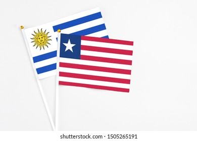 Liberia and Uruguay stick flags on white background. High quality fabric, miniature national flag. Peaceful global concept.White floor for copy space.