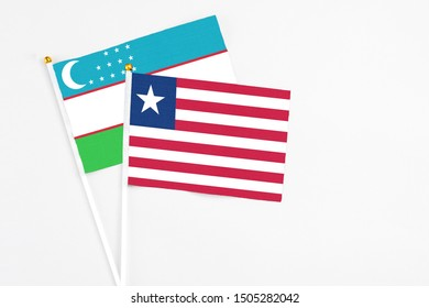 Liberia and Uzbekistan stick flags on white background. High quality fabric, miniature national flag. Peaceful global concept.White floor for copy space.
