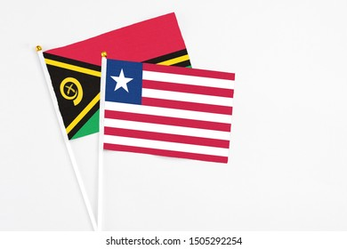 Liberia and Vanuatu stick flags on white background. High quality fabric, miniature national flag. Peaceful global concept.White floor for copy space.