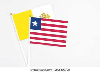 Liberia and Vatican City stick flags on white background. High quality fabric, miniature national flag. Peaceful global concept.White floor for copy space.