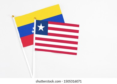 Liberia and Venezuela stick flags on white background. High quality fabric, miniature national flag. Peaceful global concept.White floor for copy space.
