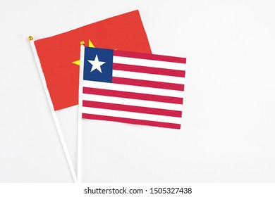 Liberia and Vietnam stick flags on white background. High quality fabric, miniature national flag. Peaceful global concept.White floor for copy space.