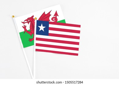 Liberia and Wales stick flags on white background. High quality fabric, miniature national flag. Peaceful global concept.White floor for copy space.
