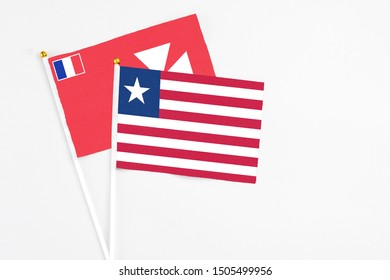 Liberia and Wallis And Futuna stick flags on white background. High quality fabric, miniature national flag. Peaceful global concept.White floor for copy space.