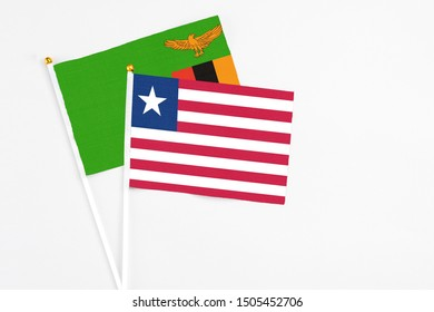 Liberia and Zambia stick flags on white background. High quality fabric, miniature national flag. Peaceful global concept.White floor for copy space.